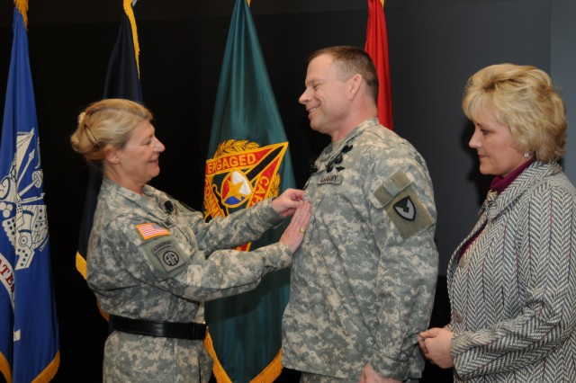 Expeditionary Contracting Command commander, Brig. Gen. Joseph L. Bass (center) is all smiles as Gen. Ann E. Dunwoody, Army Materiel Command commanding general, places his new rank on his Army Combat Uniform as his wife, Kim, watches.