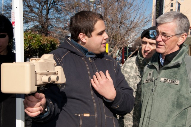 Anthony Naia, from the Communications-Electronics Research, Development and Engineering Center, demonstrates how to use Sense-Through-the-Wall technology to Secretary of the Army John M. McHugh (right) and Research, Development and Engineering Command Commander Maj. Gen. Nickolas G. Justice.