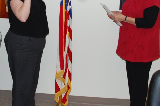 Bobbi Vaziri (right) administers the civil service oath of office to Tahee Lowery, wife of Staff Sgt. Robert Lowery. Mrs. Lowery is the first spouse hired at Fort Polk under Executive Order 13473.