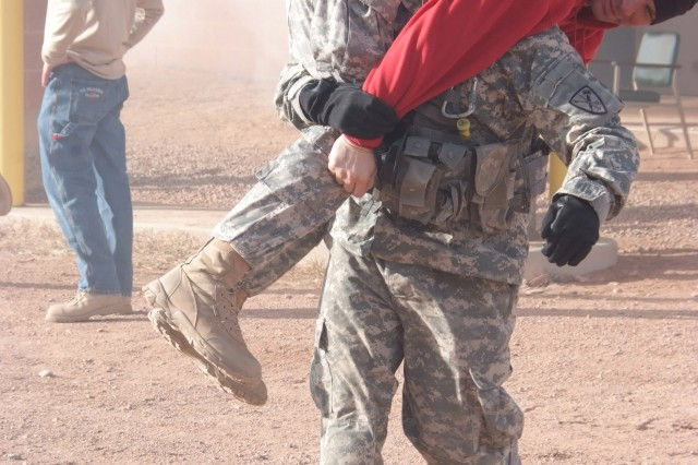 """FORT CARSON, Colo.-Staff Sgt. James Seybert fireman carries an """"injured"""" Soldier as part of a mock disaster exercise at Fort Carson Dec. 14-17."""