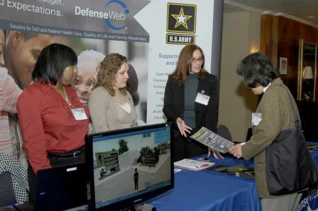 "Explaining solutions offered by DefenseWeb to an Army Family Action Plan conference attendee are, from left, program liaisons Afton Napper and Brandi Jacobs, and Projected Manager Michele Ruditis. ""We're the technical side of Army OneSource,"" Ruditis said."