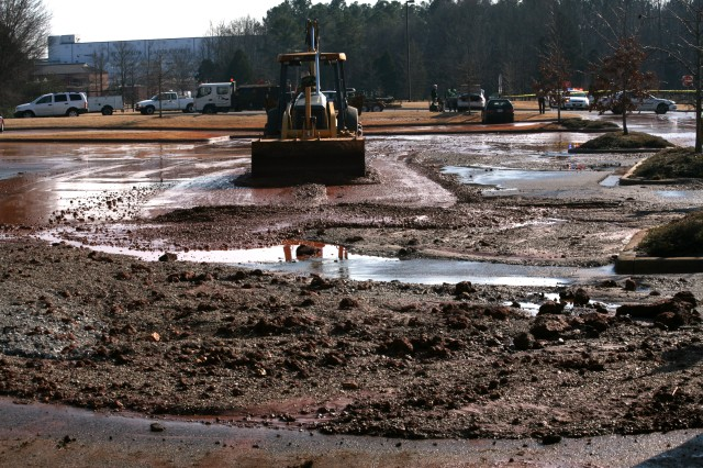 Large amounts of silt, rock and asphalt are scraped out of the U.S. Army Space and Missile Defense Command/Army Forces Strategic Command's parking lot Tuesday following a flood that nearly overtook the parking lot and caused damage to several