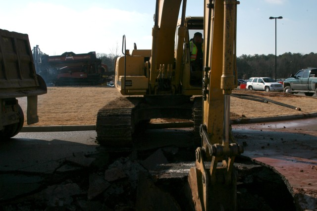 A Chugach employee digs out the damaged area in a sink hole that formed outside the U.S. Army Space and Missile Defense Command/Army Forces Strategic Command Tuesday following flooding in the parking lot.