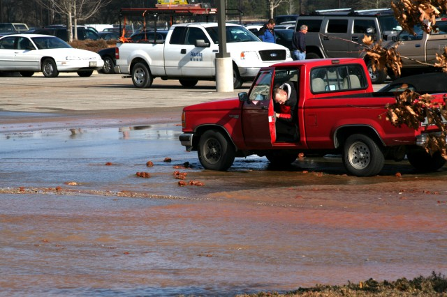 A U.S. Army Space and Missile Defense Command/Army Forces Strategic Command employee tries to guage the water depth before he attempts to drive his vehicle out of the flooded area of the parking lot Tuesday.