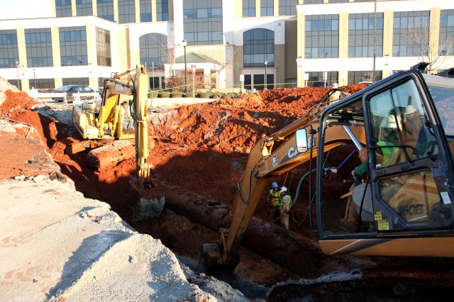 Work continues Friday on a water main line outside the U.S. Army Space and Missile Defense Command/Army Forces Strategic Command. The line burst Tuesday flooding the east parking lot.