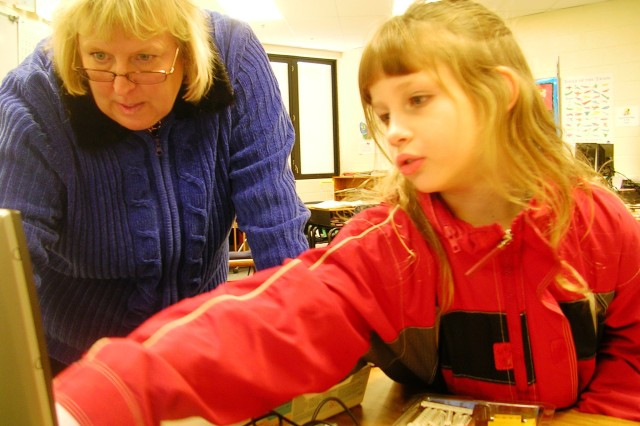 STEMS teacher Audrey Andrieski assists Sarah Porter, 7, as she works on a computer program that will be used to manipulate a LEGO robot.