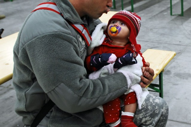 Sgt. Alexander Juvier cuddles with Megan Brown, the daughter of his battle buddy Staff Sgt. Travis Brown, prior to departing Katterbach for a twelve-month Afghanistan deployment Dec. 23.  Juvier, a Miami, Fla., native, is a logistical specialist assigned to the 5th Battalion, 158th Aviation Regiment, 12th Combat Aviation Brigade.  The baby's father deployed to Afghanistan with the main body of 5-158 troops earlier in December.