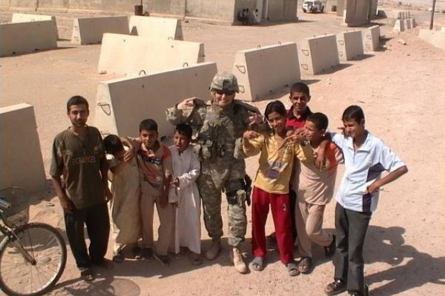 """Sgt. Sophia Malone spends time getting to know a group of Iraqi youths during her deployment to the country in 2006-07. A Texas native, Malone told the youths about her favorite college football team, the University of Texas, and tried to teach them the symbol for """"Hook'em Horns."""""""