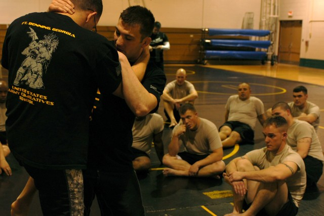 FORT CARSON, Colo. - Fort Carson Soldiers look on as Staff Sgt. Chase Lester, left, and Sgt. Steven Wyatt, combatives instructors from the U.S. States Combatives School at Fort Benning, Ga., assigned to Company D, 2nd Battalion, 29th Infantry Regiment, 197th Infantry Brigade, U.S. Army Infantry School, demonstrate techniques to deflect an opponent's knee during Modern Army Combatives Program Level III training at Garcia Physical Fitness Center Jan. 12. After completing the course, the Mountain Post Soldiers will be certified to pass on their skills, training and techniques to their Soldiers and units. (U.S. Army photo by Pfc. Andrew Ingram, 4th Inf. Div. PAO)