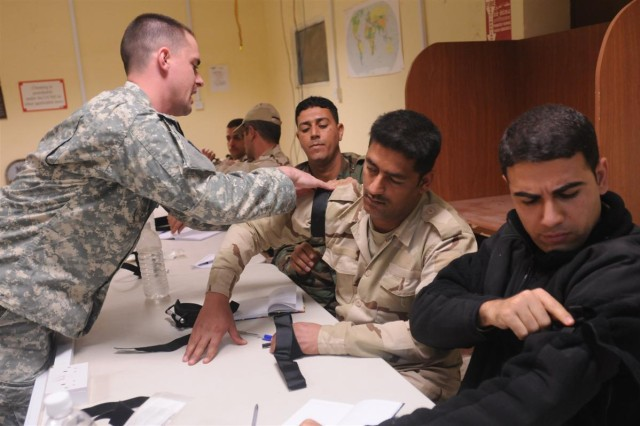 Spc. Christopher Graham, a brigade medic and health specialist with the 96th Sustainment Brigade, 13th Sustainment Command (Expeditionary), and a Pleasant Grove, Utah, native, assists Iraqi medical officers with the use and application of a tourniquet. Graham was an instructor teaching combat medical procedures to staff members Jan. 12 through Jan. 14 at Taji Location Command Medical Clinic level 2 at Camp Taji, Iraq.