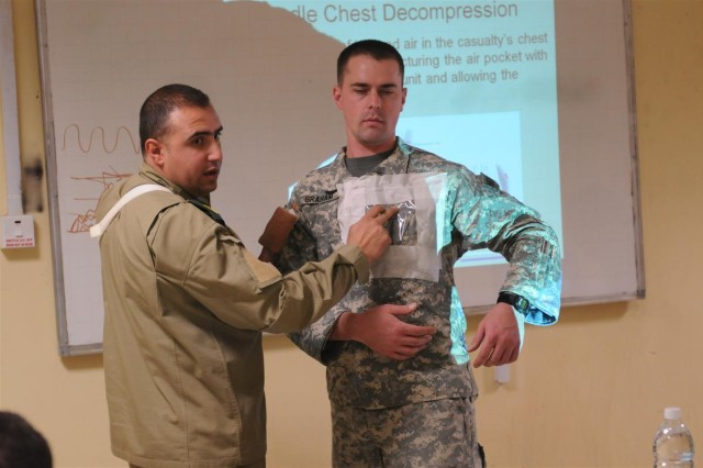 Maj. Adnan Najji, a senior medical officer and commander of the Taji Location Command Medical Clinic level 2, explains, in Arabic, the technique and rules to applying a needle chest decompression, using Spc. Christopher Graham, a brigade medic and health specialist with the 96th Sustainment Brigade, 13th Sustainment Command (Expeditionary), and a Pleasant Grove, Utah, native, as a demonstrator Jan. 12 at Camp Taji, Iraq.