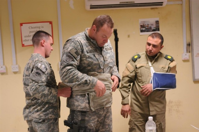 Maj. Adnan Naji, a senior medical officer and commander of the Taji Location Command Medical Clinic level 2, explains, in Arabic, the technique used by Spc. Christopher Graham, a brigade medic and health specialist with the 96th Sustainment Brigade, 13th Sustainment Command (Expeditionary), and a Pleasant Grove, Utah, native, to apply bandages to a simulated open abdominal wound on Staff Sgt. Michael Carlson, a medic with the 1161st Task Force, 541st Combat Sustainment Support Battalion, 96th Sust. Bde., 13th ESC and a Yakima, Wash., native, Jan. 13 at Camp Taji, Iraq. Carlson and Graham are instructors training Iraqi Army medical officers on combat medical procedures at Camp Taji.