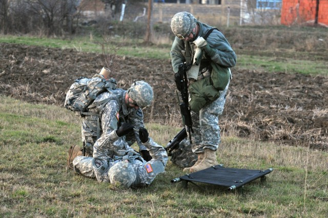 Sgt. 1st Class Steven B. Ybarra, Santa Clarita, Calif., and Sgt. Arthur J. Lynch, Alhambra, Calif., rush to give aid to a Soldier with simulated injuries during a Quick Reaction Force validation exercise. Both Soldiers of Multi-National Task Force-East, 1-144th Maneuver Task Force, were tested in two separate simulated incidents Jan. 13 in Kosovo.