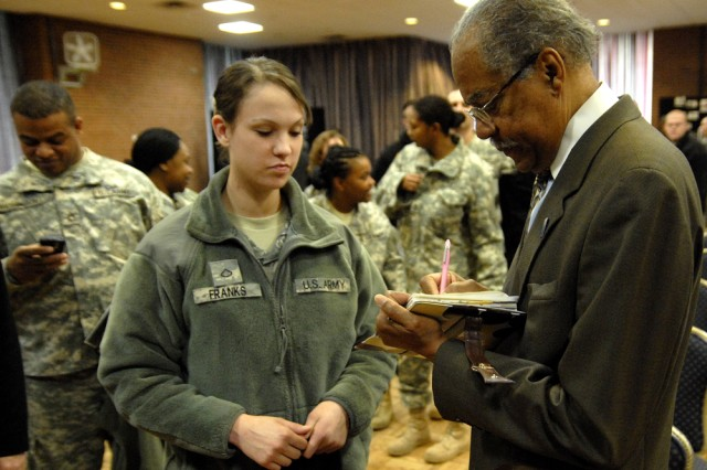 Pfc. Jlynn Franks of the 289th MP Company gets her program signed by Rev. Samuel Kyles during the Martin Luther King Jr. prayer breakfast at the Joint Base Myer-Henderson Hall Community Center Tuesday.