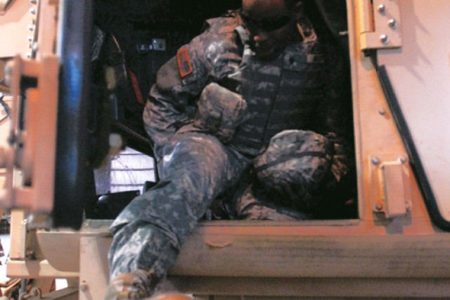 A Soldier climbs out of the driver's side door of the upside down Humvee.