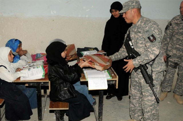 Staff Sgt. Mario A. Bonilla, a training noncommissioned officer with the 36th Sustainment Brigade, out of Temple, Texas, 13th Sustainment Command (Expeditionary) delivers school supplies to a student Jan. 13, at Ibn Rushed School, near Nasariyah, Iraq. Soldiers with the 36th Sust. Bde. visited to distribute school supplies to the students and teachers to further the Iraqi civil capacity and aid the next generation of Iraqi leaders.