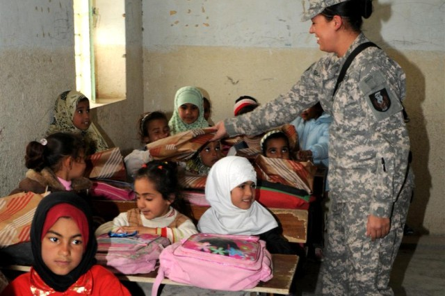 Staff Sgt. Nikki Shearman, a human resources noncommissioned officer with the 36th Sustainment Brigade, out of Temple, Texas, 13th Sustainment Command (Expeditionary) and a Fort Worth, Texas, native, delivers school supplies to a student Jan. 13, at Ibn Rushed School, near Nasariyah, Iraq. Soldiers with the 36th Sust. Bde. visited to distribute school supplies to the students and teachers to further the Iraqi civil capacity and aid the next generation of Iraqi leaders..