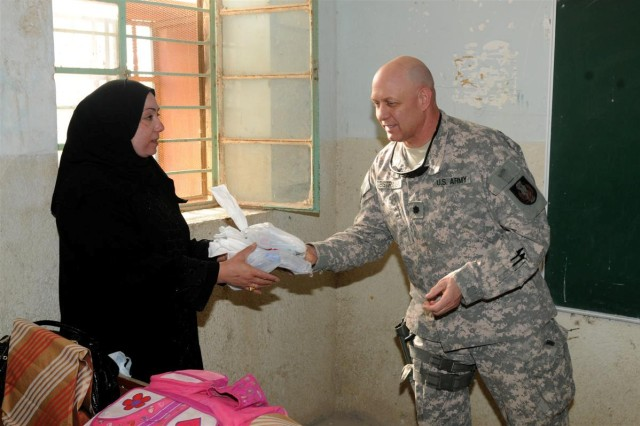 Lt. Col. Peter M. Bistransin, the civil military officer with the 36th Sustainment Brigade, out of Temple, Texas, 13th Sustainment Command (Expeditionary) and an Austin, Texas, native, delivers school supplies to a teacher at Ibn Rushed School Jan. 13, near Nasariyah, Iraq. The 36th Sus t. Bde. Soldiers visited to distribute school supplies to the students and teachers to further the Iraqi civil capacity and aid the next generation of Iraqi leaders.