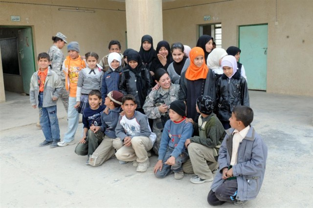 Staff Sgt. Imelda P. Quiroz, the supply accounting noncommissioned officer with the 36th Sustainment Brigade, out of Temple, Texas, 13th Sustainment Command (Expeditionary) poses for a picture with the students at Ibn Rushed School Jan. 13 near Nasariyah, Iraq. She said the visit reminded her of humanitarian visits to the school she attended when she lived Ciudad Acuña, Mexico as a child.