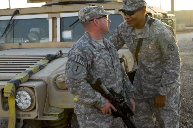 BAGHDAD - Sgt. 1st Class Mike Street (left), of Charlotte, N.C., and 1st Lt. Carlos Gonzalez, of Greenville, N.C., hold a conversation in front of the tactical operations center at Camp Stryker, south of Baghdad, just as their shift ends. (U.S. Army Photo by Spc. Ruth McClary, 30th HBCT PAO, USD-C)