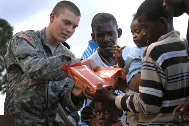 Army Spc. Brent Nailor, 1st Squadron, 73rd Cavalry Regiment, 82nd Airborne Division, passes out humanitarian aid meals to women and children in Port-au-Prince, Haiti, Jan. 16, 2010. The squadron established a forward operating base at an abandoned, damaged country club near the embassy. A survivor camp of thousands is situated near the based.
