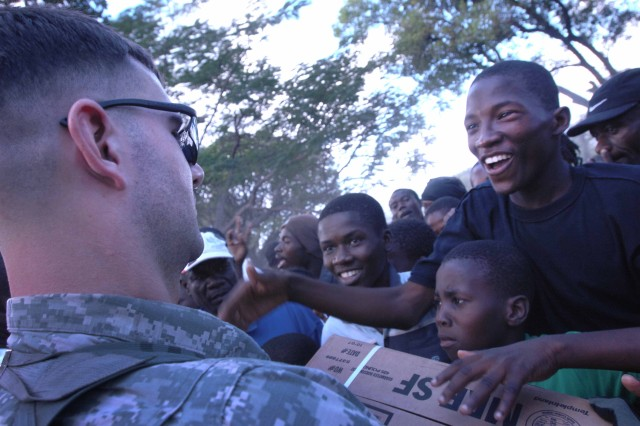 A large crowd swarms around U.S. troops as they walk into a survivor camp with food in Port-au-Prince, Haiti, Jan. 16, 2010. The soldiers, assigned to the 82nd Airborne Division's 1st Squadron, 73rd Cavalry Regiment, distributed more than 2,500 meals after the people.