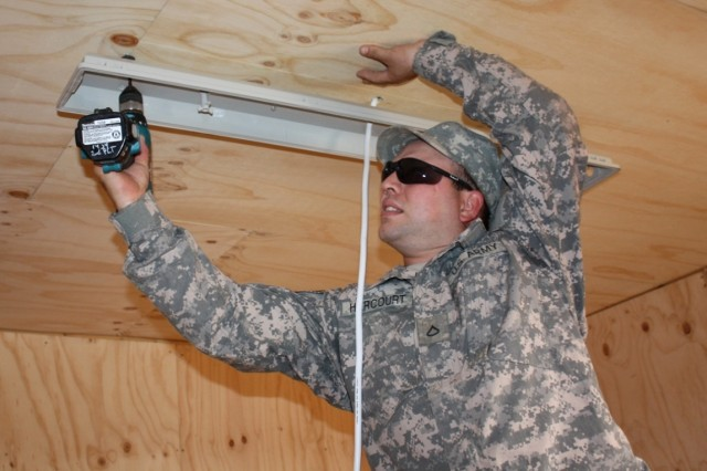 BAGHDAD- Pvt. 1st Class Jessie Harcourt, an Soldier in the 1434th Engineer Company, 101st Eng. Battalion, from Elmira, Mi., installs a light fixture in the new planning annex at COS Carver on Dec. 31. When complete, the new structure will help U.S. and Iraqi forces to better plan joint missions.  (U.S. Army photo by Staff Sgt. April Mota, 101st Engr. Bn. UPAR, 16th Eng. Bde., USD-C)