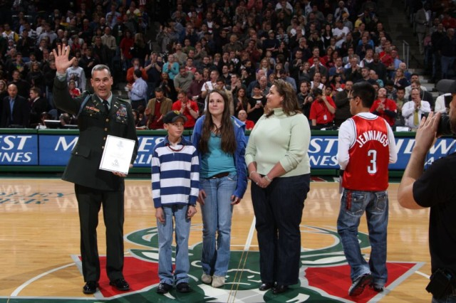 Colonel Brian E. Winski, Commander, 4th Brigade Combat Team, 1st Cavalry Division and family are honored prior to the start of the Milwaukee Bucks game on December 26th, 2009 in Milwaukee, Wisconsin.  Pictured with Colonel Winski are his son Andrew, daughter Kathryn, and wife Kimberly from left to right.