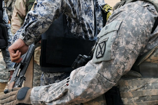 BAGHDAD - Staff Sgt. Johnny Ferree, a platoon sergeant with Task Force Nassir, helps an Iraqi Federal Policeman clear his weapon during reflexive fire training Jan. 13. The Iraqi-led training, part of a two-week course at Contingency Operating Station Cashe South, is meant to enhance the combat and leadership skills of policemen in Baghdad. (U.S. Army photo by Staff Sgt. Jeff Hansen, 366th MPAD, USD-C)