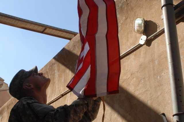 BAGHDAD, Iraq - Wichita, Kan., native, 1st Lt. Ryan Zeller, an infantry officer assigned to Headquarters and Headquarters Company, 1st Brigade Special Troops Battalion, 1st Brigade Combat Team, 1st Cavalry Division, raises a flag during a visit with his brother Sgt. Kyle Zeller, an infantry team leader assigned to the 2nd Battalion, 7th Infantry Regiment, 1st Brigade Combat Team, 3rd Infantry Division, at the Al Faw Palace in Baghdad Jan. 6.