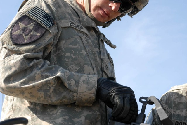 CAMP TAJI, Iraq - Columbiana, Ala., native Spc. Brandon Bishop, the number two man on a howitzer crew assigned to 2nd Battalion, 12th Field Artillery Regiment, 4th Stryker Brigade Combat Team, 2nd Infantry Division, performs a functions check on the breach of an M777 howitzer. The crew supported 1st Brigade Combat Team, 1st Cavalry Division, during a joint fires exercise Jan. 10.