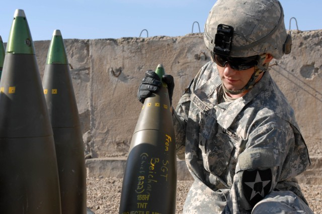 CAMP TAJI, Iraq - Brooksfield, Fla., native Sgt. Joseph Beichner, chief of a howitzer crew assigned to 2nd Battalion, 12th Field Artillery Regiment, 4th Stryker Brigade Combat Team, 2nd Infantry Division, places a 155mm round back in place after he marks it with his signature. The crew supported 1st Brigade Combat Team, 1st Cavalry Division, during a joint fires exercise Jan. 10.