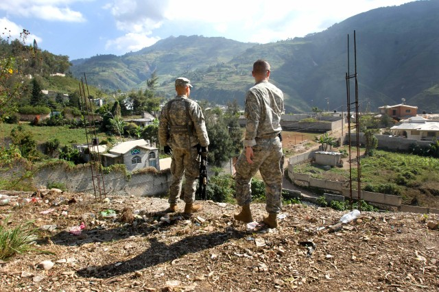 Capt. Buddy Davis, a physician assistant, and Staff Sgt. Fabian Acosta, a human intelligence specialist, survey a possible helicopter landing zone near a hospital in Port-au-Prince, Haiti, Jan. 18, 2010. Davis and Acosta are assigned to the 82nd Airborne's 1st Squadron, 73rd Cavalry Regiment. The two visited an area hospital trying to find a place to send critical patients who show up at the forward operating base the squadron has established in the city.