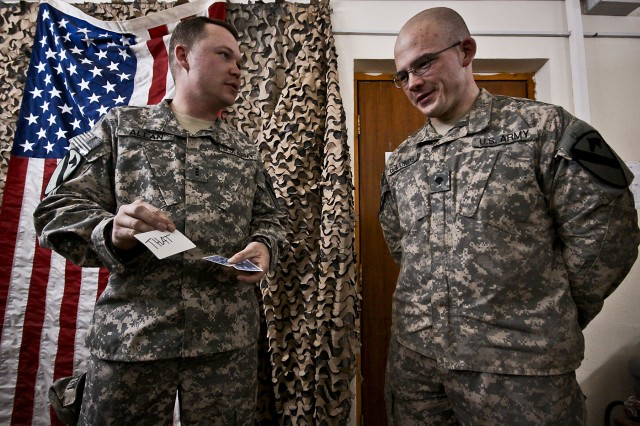 CAMP TAJI, Iraq - Chief Warrant Officer 3 Michael Allan (left), a Marysvale, Utah, unmanned aerial vehicle technician for Quick Reaction Capability 1, pulls a card trick on a surprised Spc. Timothy Edmonds, from Elmwood, Tenn., a paralegal specialist with 1st Air Cavalry Brigade Jan 13. (U.S. Army photo by Sgt. Travis Zielinski, 1st ACB, 1st Cav. Div., USD-C).