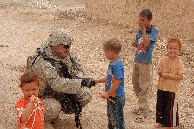 BAGHDAD - Staff Sgt. Travers Brake, a native of Elkins, W.Va., and a platoon sergeant assigned to Troop C, 1st Battalion, 150th Armored Reconnaissance Squadron, 30th Heavy Brigade Combat Team, 1st Armored Division, makes Iraqi children smile when he hands them pencils during a mission to the Zwaynot village. (Photo courtesy of Staff Sgt. Travers Brake)
