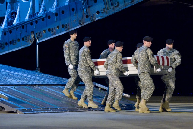 Staff Sgt. Bradley Falls and his casket team of Company D, 1st Battalion, ensure the dignified transfer of the remains of Army Spc. Brian R. Bowman of Crawfordsville, Ind., at Dover Air Force Base, Del., January 04, 2010.