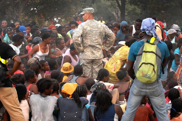Army Capt. Jon Hartsock stands in a crowd of women waiting for food and water to be distributed in Port-au-Prince, Haiti, Jan. 19, 2010. Hartsock is assigned to the 82nd Airborne's 1st Squadron, 73rd Cavalry Regiment, and runs the day-to-day distribution of humanitarian aid.