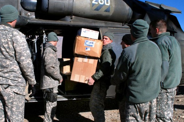 Sgt. Matthew West removes boxes of supplies from the back of a Black Hawk helicopter to be delivered to schools in and around Bamyan province in Afghanistan, Jan. 13, 2010.
