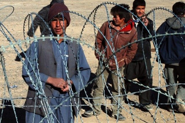 Qugamali, an 18-year-old Afghan who teaches English classes in the Bamyan province of Afghanistan, talks over the concertina wire with U.S. Soldiers explaining what he does and the supplies he needs, Jan. 13, 2010.