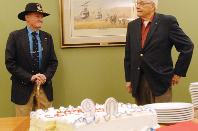 CSM(R) Basil Plumley, R, stands in front of a Vietnam War print, donated to the National Infantry Museum during a belated 90th birthday celebration Monday.  Also pictured is LTG(R) Hal Moore.