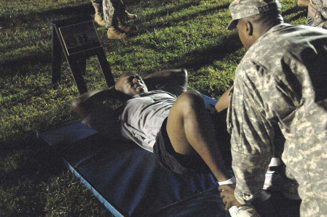In this file photo, Staff Sgt. Julian Wiggins, U.S. Army Medical Command, focuses on the sit-up portion of the APFT Oct. 1, during the 2008 Department of the Army NCO/Soldier of the Year Competition at Fort Lee, Va.