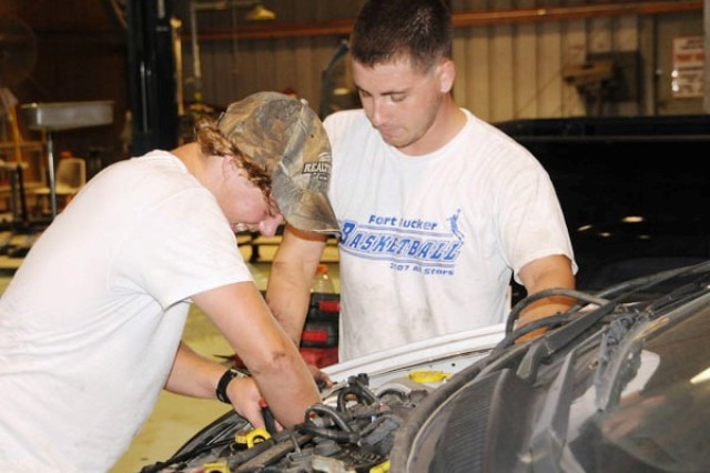 Josh Eastburn, left, finishes an engine replacement with Fort Rucker Automotive Skills Center mechanic Brandon Curry last July. Eastburn found his job there through the HIRED! program, an Armywide resource helping teens find employment.