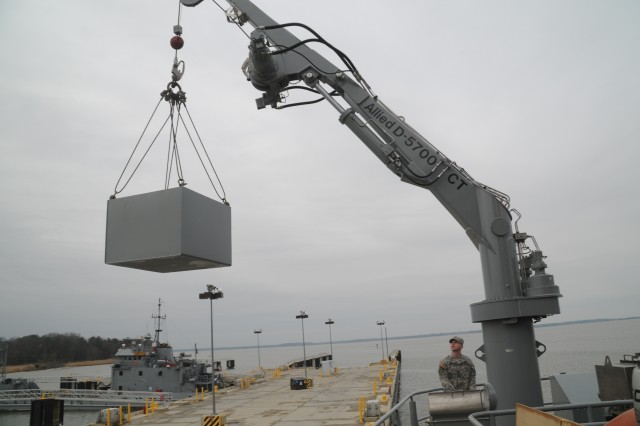 Specialist Aaron Cooper, a watercraft operator with the 335th Transportation Detachment, 24 Transportation Battalion, 7th Sustainment Brigade, 3d Sustainment Command (Expeditionary) uses a hydraulic crane to lift supplies aboard LSV 1 before departing to provide disaster relief in Haiti at Fort Eustis' 3rd Port  Jan. 21.  (U.S. Army photo by Sgt R.J. Gilbert)