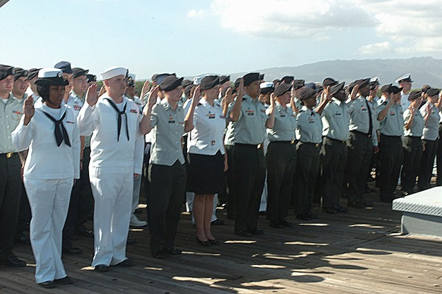 """Soldiers, Sailors, Airmen and Marines raise their right hands as they recite the oath of enlistment during a multi-service re-enlistment ceremony aboard the main deck of the historic EX-USS Missouri while traveling to Ford Island's """"Battleship Row,"""" Jan. 7. Following the ceremony, all members aboard the """"Mighty Mo"""" were invited to man the rails as the ship nestled comfortably back home at the USS Missouri Memorial, greeted by friends, family and well-wishers awaiting the battleship's return at the dock. (U.S. Army photo by Spc. Mahlet Tesfaye, 25th Infantry Division Public Affairs Office.)"""