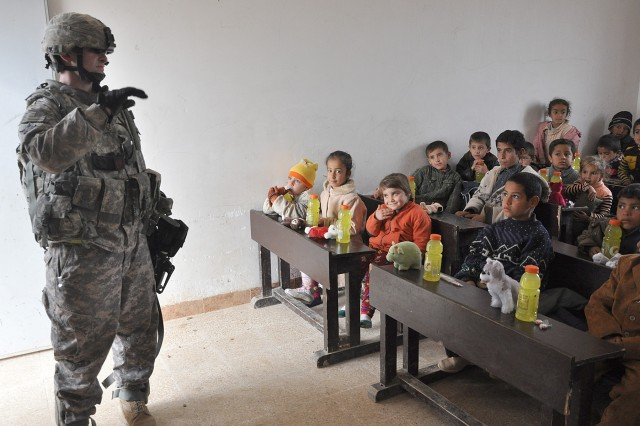 Staff Sgt. Stuart Gimble, the personal security detachment platoon sergeant, waves to Iraqi students during a visit to their school Jan. 20 in the village of Jedellah Sofla, near Contingency Operating Location Q-West, Iraq. (U.S. Army photo by Staff Sgt. Rob Strain, 15th Sustainment Brigade Public Affairs)