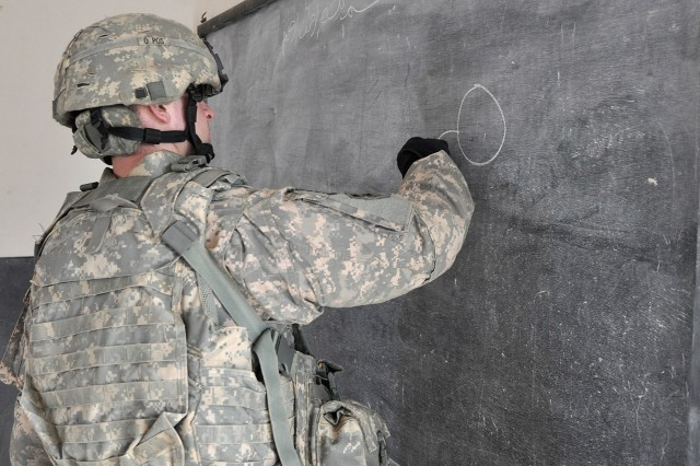 Staff Sgt. Stuart Gimble, the personal security detachment platoon sergeant, draws on the chalkboard for Iraqi students during a visit to their school Jan. 20 in the village of Jedellah Sofla, near Contingency Operating Location Q-West, Iraq. (U.S. Army photo by Staff Sgt. Rob Strain, 15th Sustainment Brigade Public Affairs)