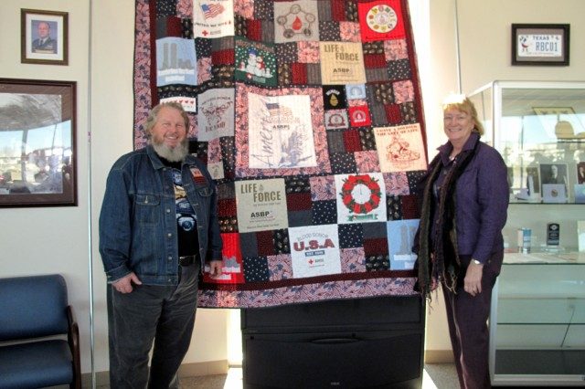 Mr. and Mrs. Robert Boswell with the quilt that Mrs. Boswell sewed using blood donation tee shirts given to her husband.  Robertson Blood Center at Fort Hood. January 21, 2010.