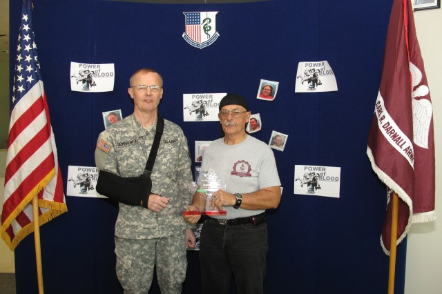 LTC Dennis Dombrowski, director of the Robertson Blood Center at Fort Hood presents the donor of the year trophy to Mr. Ronald Decker January 21, 2010.