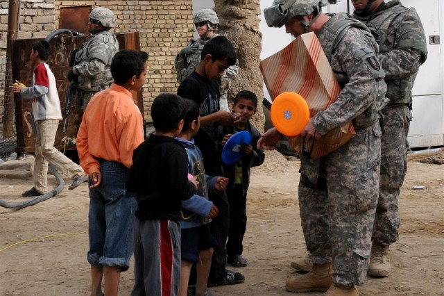 Lt. Col. Peter M. Bistransin, the civil military officer with the 36th Sustainment Brigade out of Temple, Texas, 13th Sustainment Command (Expeditionary) and an Austin, Texas, native, hands out Frisbees to some of the local children Jan. 18 at one of the water pumps on the Euphrates River that supplies water to Camp Adder, Iraq.