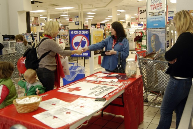 Stephanie Luce, the Fort Irwin Red Cross station manager, hands a business card to a military spouse during a volunteer drive at the Post Exchange at Fort Irwin, Calif., Jan. 16. (Photo by Sgt. Giancarlo Casem, 11th ACR Public Affairs)
